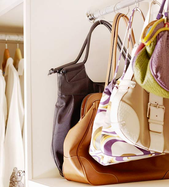 I always have a hard time storing purses. If I put them in a box, I forget about them. If they sit on a shelf they just fall out all over the place. Better Homes and Gardens uses a tension rod and shower curtain rings to display purses, found over here.