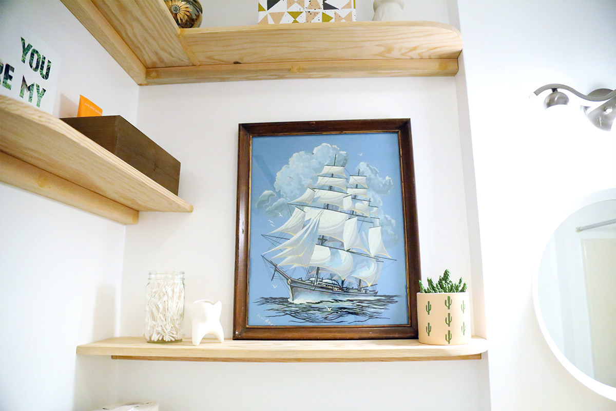 Close up of DIY shelves with framed artwork of ship.