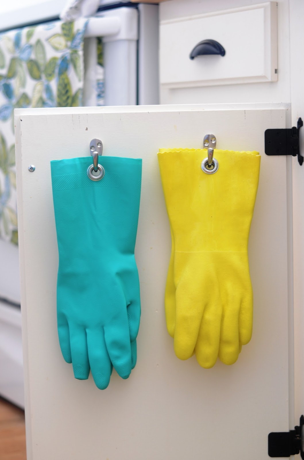 Add grommets to your rubber gloves to hang them inside a cupboard door, found on Iron and Twine.