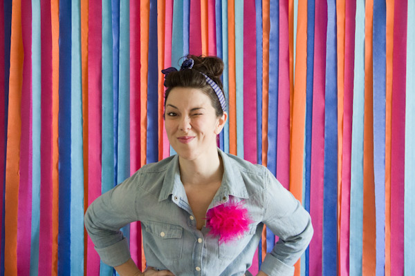 This photo backdrop is easy on the budget. A variety of colored crepe paper make this cute backdrop, from Lovely Indeed.