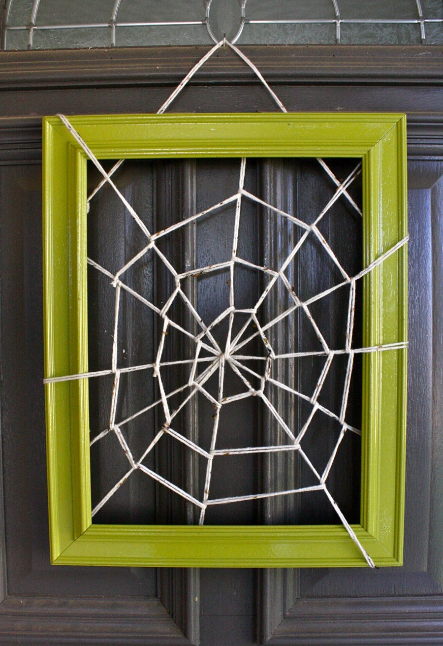 Use an old frame and some yarn to make this spiderweb door hanging, on Dana Made It.
