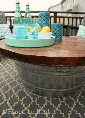 Make a outdoor storage coffee table with a giant bucket and some wood, from A Place to Nest.