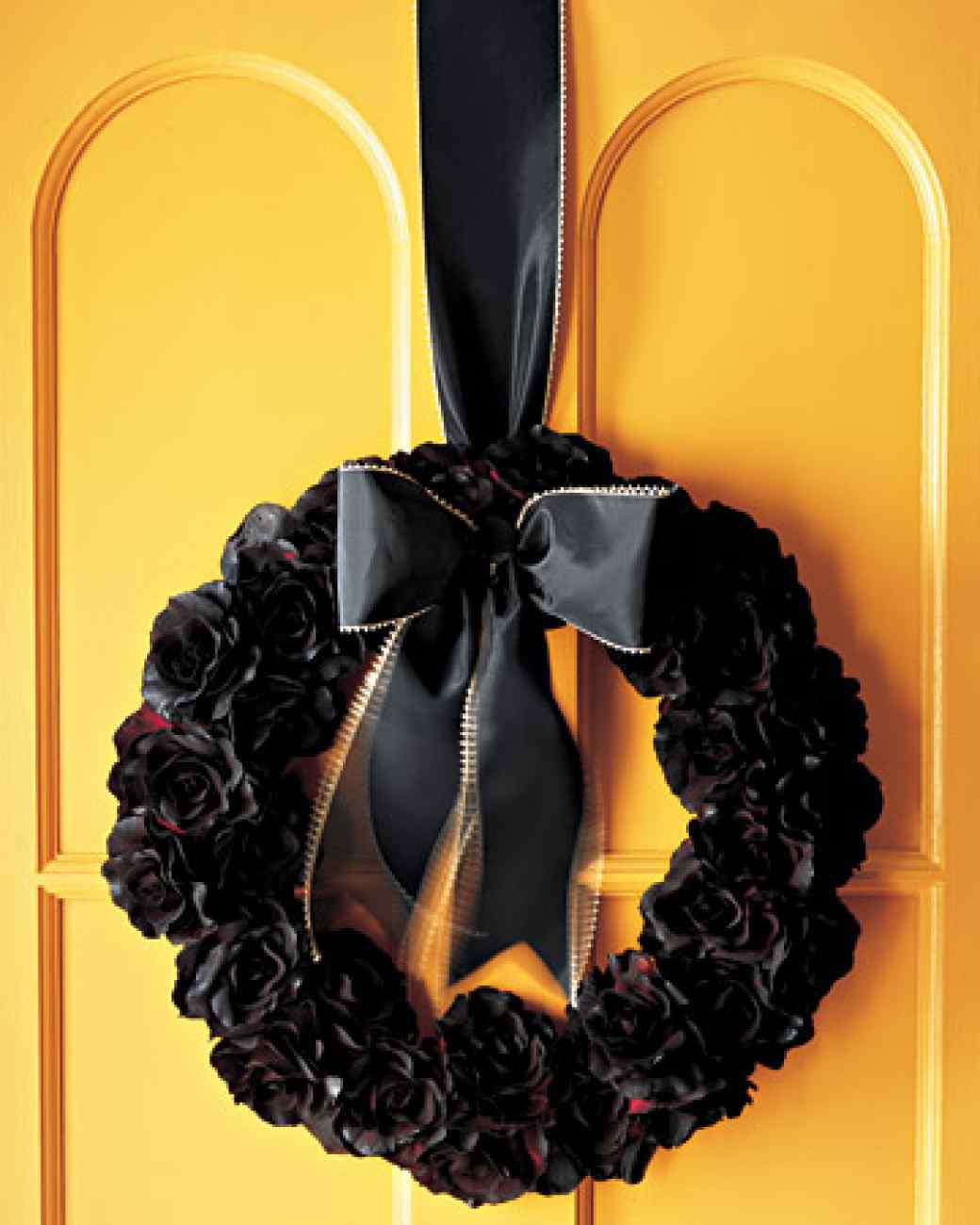 Spray painting these flowers black really makes this a Halloween Wreath, on Martha Stewart.