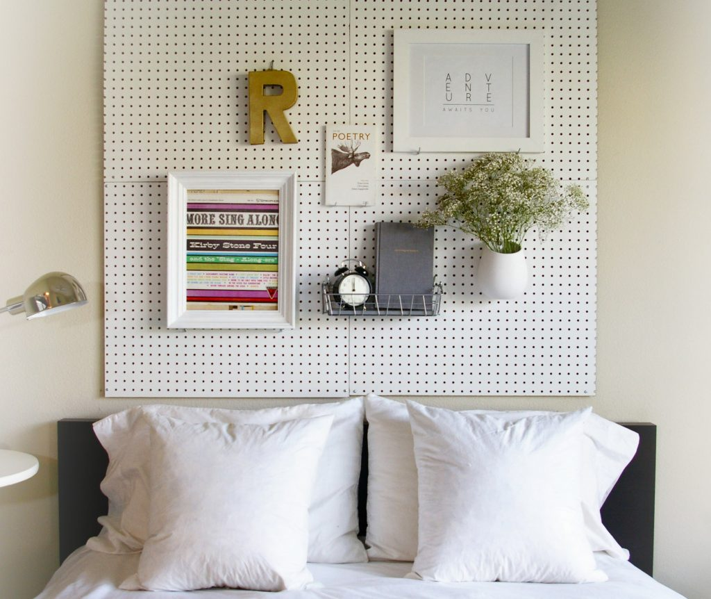 This pegboard headboard gives you the option to move things around. Easily switch out artwork and shelving. Found on Sugar and Cloth.